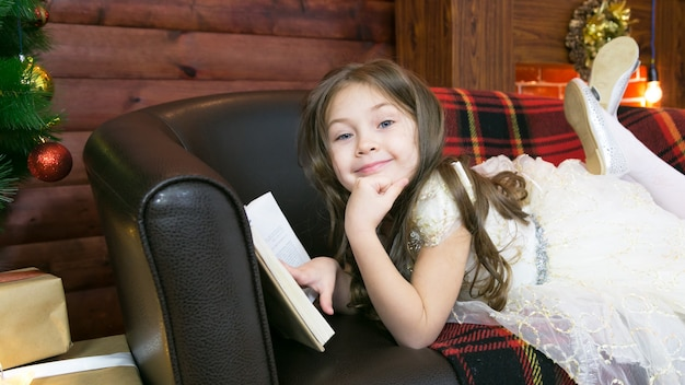 A child reads an interesting book by the christmas tree.