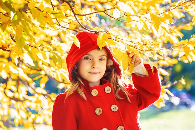 Child in a red coat with autumn leaves. love autumn. selective focus.