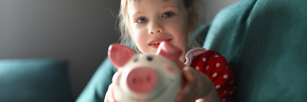 Child in red dress hold pink piggy bank in her hands