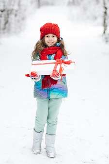 Child in red hat with christmas presents and gifts in snow.