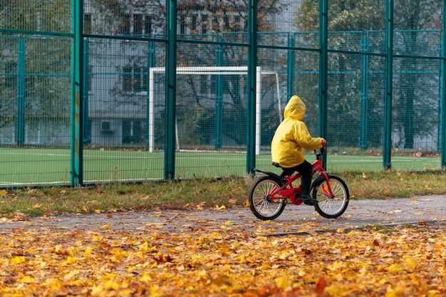 Велосипед езды ребенка на детской площадке на желтом фоне опавших листьев. мальчик в желтом пальто. осенний день