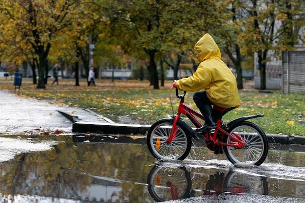 Ребенок едет на велосипеде под дождем и по лужам. мальчик в желтом плаще один катается по лужам.