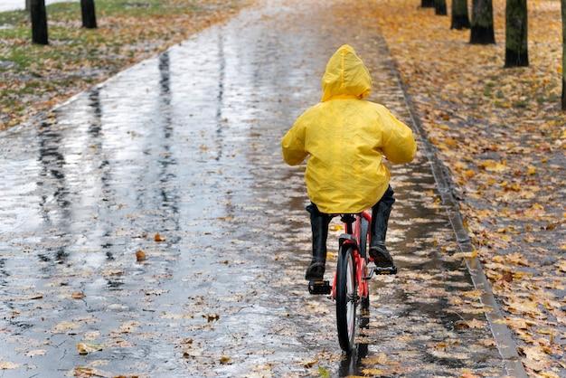 Ребенок едет на велосипеде под дождем в осеннем парке. ребенок в желтом плаще. вид сзади.
