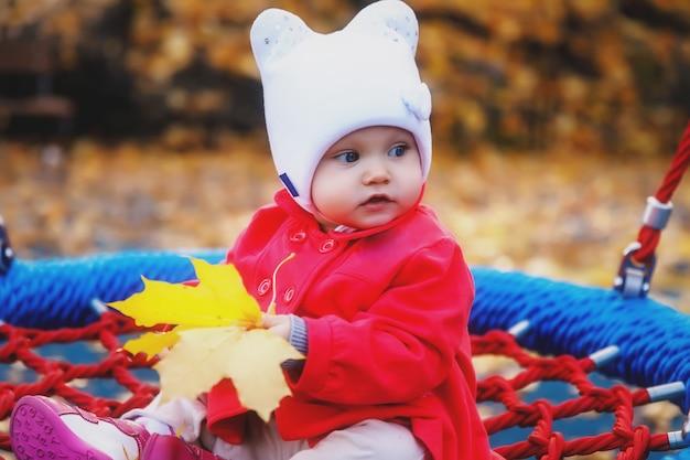 Ребенок катается на качелях с желтыми осенними листьями