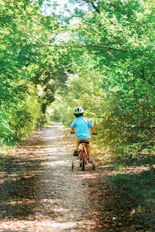 Child riding a bicycle. kid in a helmet riding a bike in the forest.