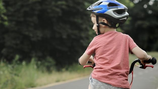 Ребенок, езда на велосипеде по велосипедной дорожке под дождем. ребенок в шлеме учится ездить летом. счастливый мальчик езда на велосипеде, развлекаясь на открытом воздухе на природе. активный спорт, семейный отдых