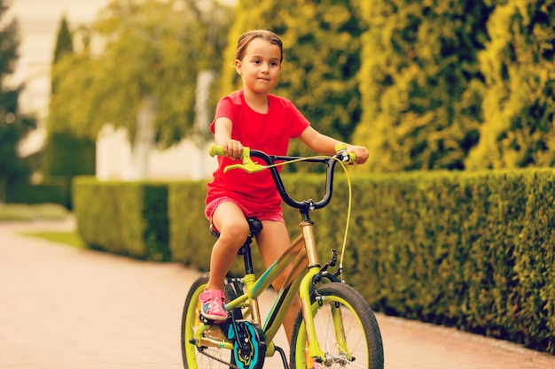 Child riding bike. kid on bicycle in sunny park.