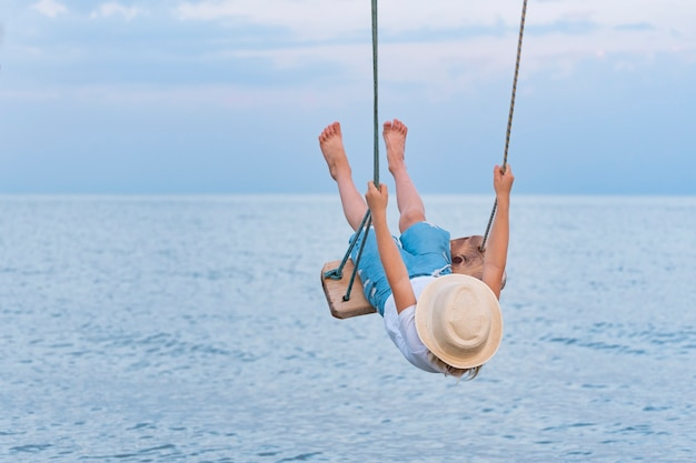 Child riding on rope swing over the water and lifted high legs. vacation at sea.