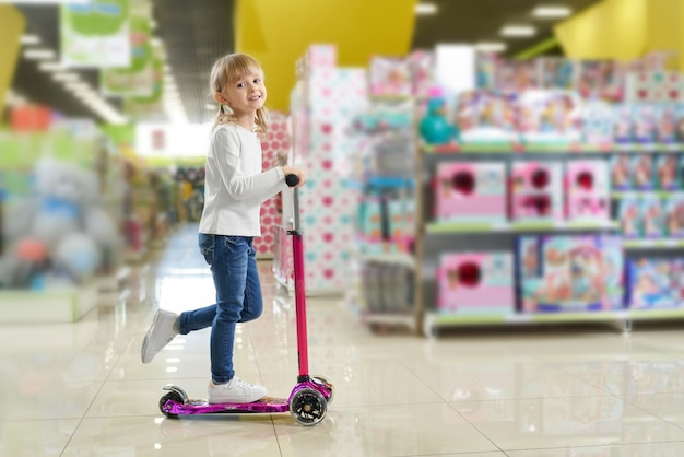 Child riding scooter in big store with toys.
