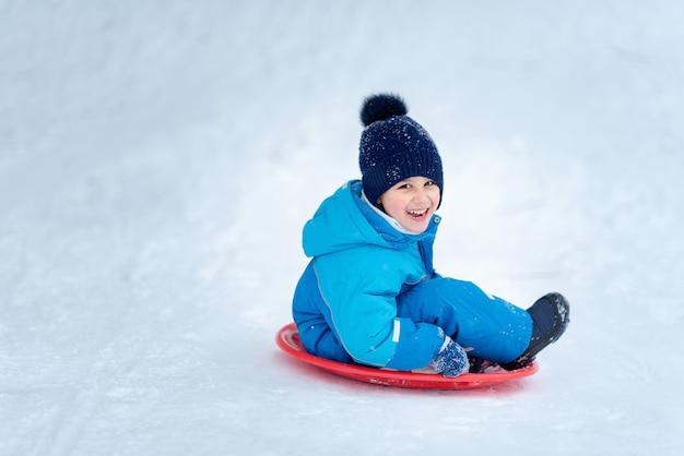 Child rolls down a snow hill. boy sliding down snow hill in winter.