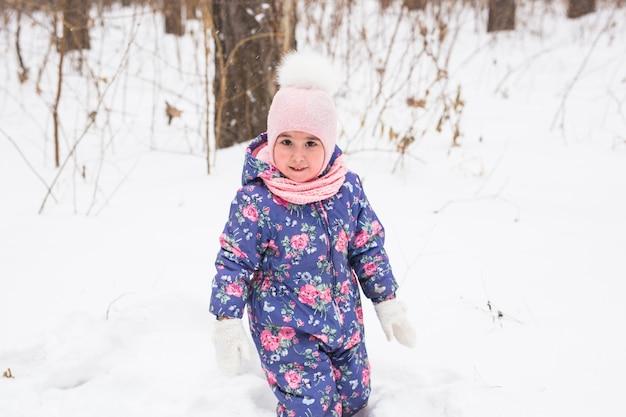 Ребенок работает в снежном лесу. малыш ребенок играет на открытом воздухе. ребенок играет в снежном парке.