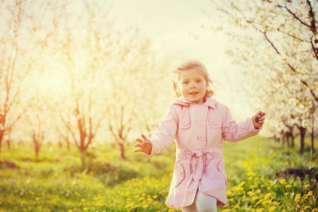야외에서 꽃 나무를 실행하는 아이.