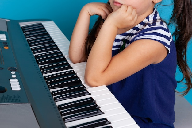 Child's elbows pressing or playing music on the piano keys