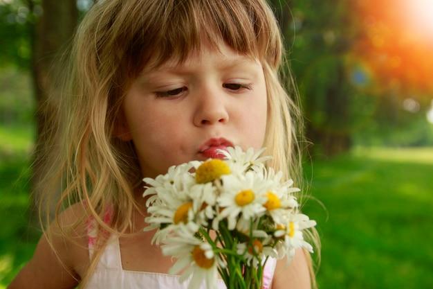 自然公園で花の花束と舌幸せな女の子の子供を示す子供の感情