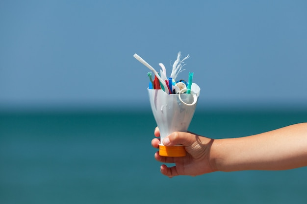 Child's hand on background of sea holds plastic garbage collected on beach. concept - excessive consumption of disposable packaging, pollution of world's oceans with microplastics.