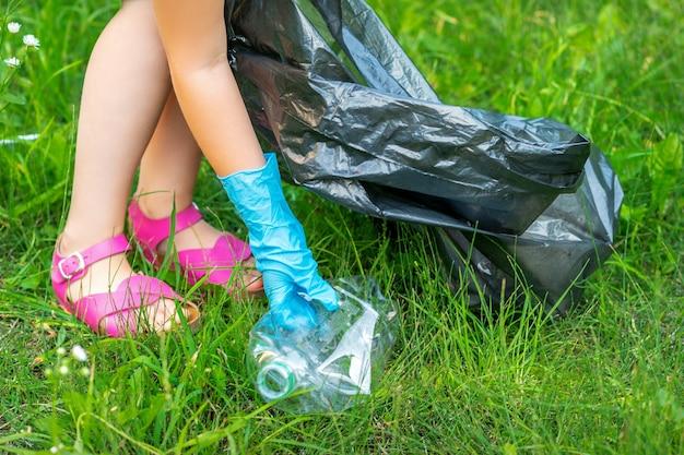 子供の手が公園の芝生にあるプラスチック製の道具から公園を掃除します