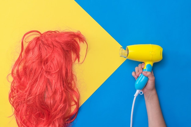 The child's hand directs the hair dryer to the bright orange wig. hair care concept. create a new style.