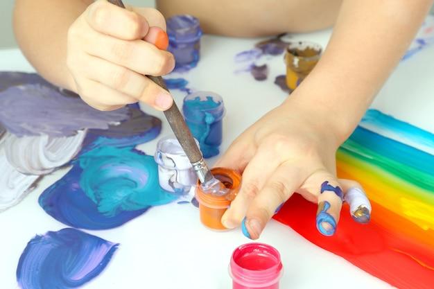 어린이의 손은 흰색 배경에 그림 색상을 그립니다. 그림 분야의 어린이 창의력