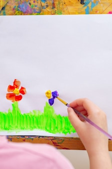 イーゼルの白い紙に花を描く子供の手。子供とアースデイのコンセプト。