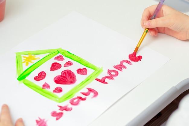 自宅で白い紙に水彩絵の具でブラシで外出禁止令と心の家を描く子供の手。家にいるコンセプト。