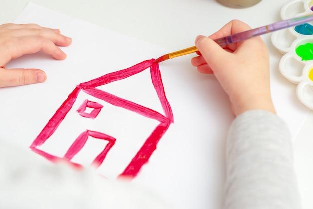 Рука ребенка, рисующая дом