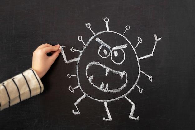 Рука ребенка рисует белым мелом на школьной доске.
