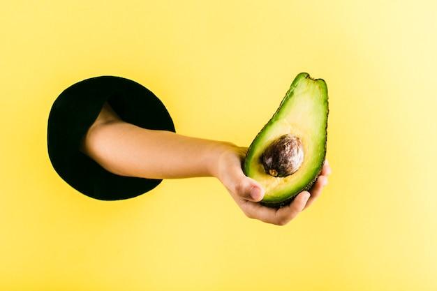 Рука ребенка держит авокадо из черной дыры в желтой бумажной стене