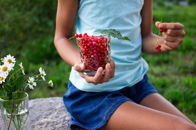 Рука ребенка, держащая стакан, полный красной смородины летом на открытом воздухе в саду