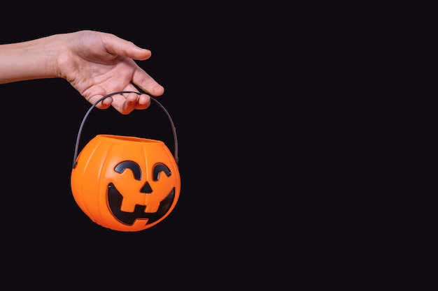 Child's hand holding orange pumpkin basket, jack lantern isolated on black background. waiting for halloween candies. trick or treat tradition. happy halloween concept