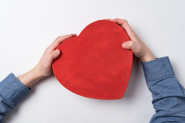 Child's hand holding red box in heart shape on white wall. top view. copy space.