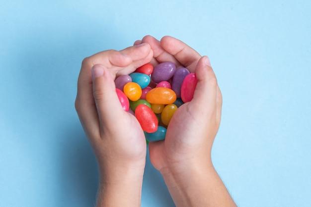 파란색 표면에 여러 젤리 콩을 들고 아이의 손