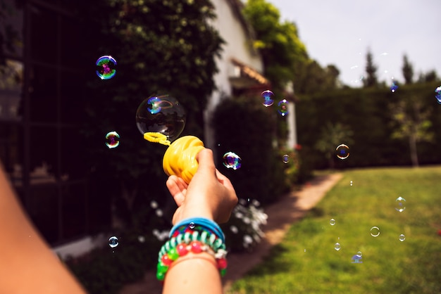 Child's hand holding a soap bubble while playing in summer.