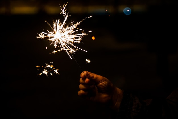 Child's hand holding a sparkler that sizzles and shines during the night.