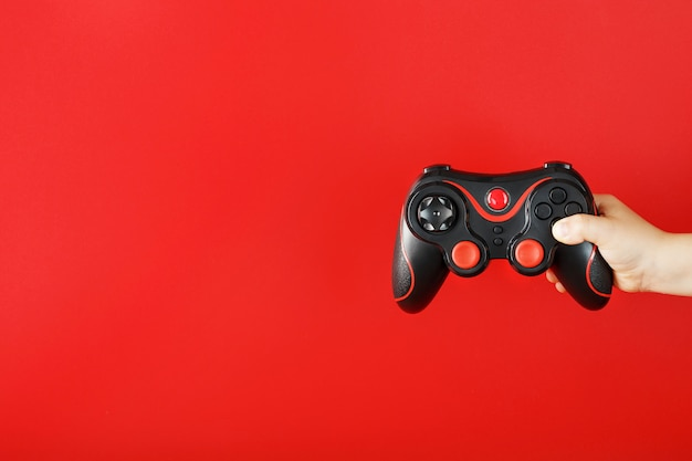 Child's hand holds a gamepad on a red surface