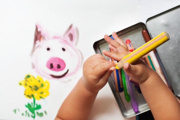 Рука ребенка рисует красочными карандашами. вид сверху.