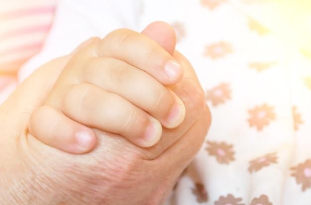 Детская рука рукопожатия малыша руки взрослого человека. понятие об отношениях бабушки и внуков.