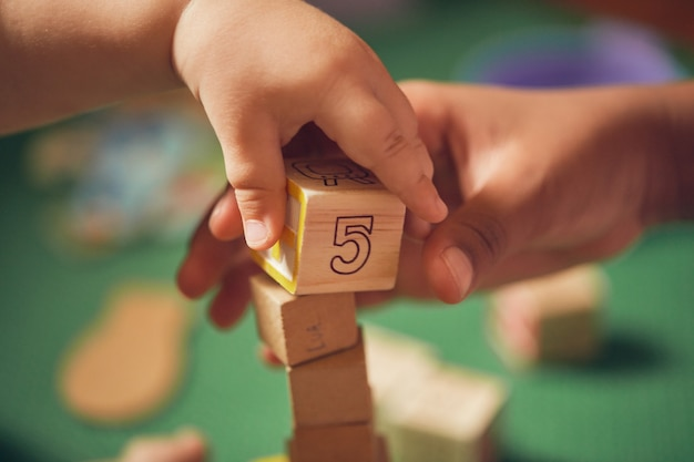 Child's hand picking up a wooden block with the number 5