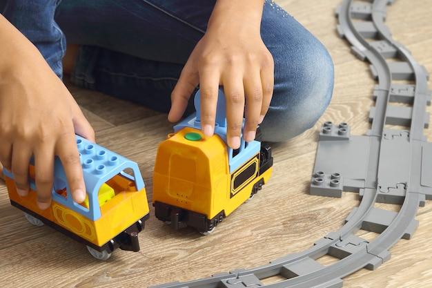 어린이 철도를 가지고 노는 어린이의 손. 게임과 어린이 창의력 발달