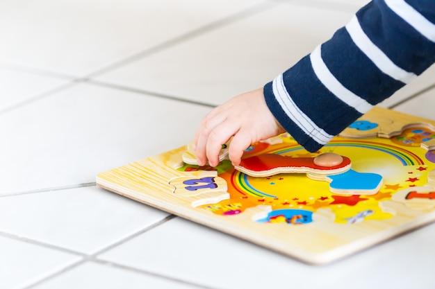 La mano di un bambino che gioca con un puzzle orologio in legno in soft focus