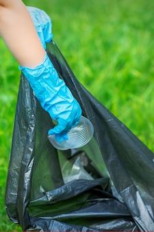 子供の手が公園のゴミ袋にプラスチックの破片を入れます