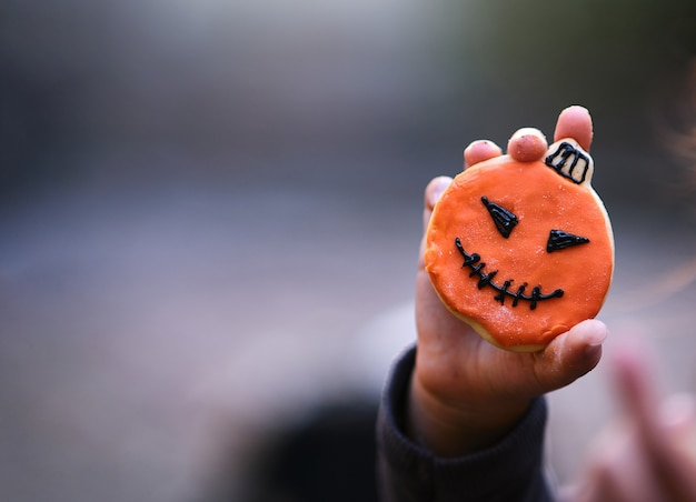 Child's hand showing a decorated halloween cookie