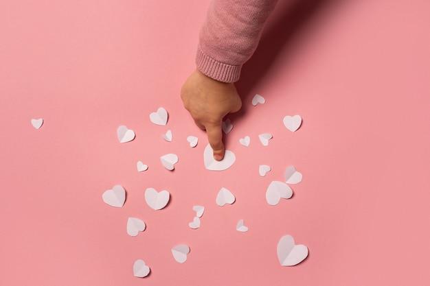 子供の手はピンクの背景の紙からバレンタインカードを取ります。作曲バレンタインデー。バナー。フラットレイ、上面図。