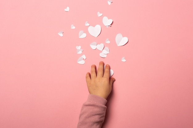 어린이 손에 분홍색 배경에 종이에서 발렌타인 카드를 걸립니다. 구성 발렌타인 데이. 배너. 평면 평신도, 평면도.