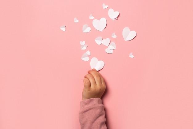 Рука ребенка берет валентинку из бумаги на розовом фоне. композиция ко дню святого валентина. баннер. плоская планировка, вид сверху.