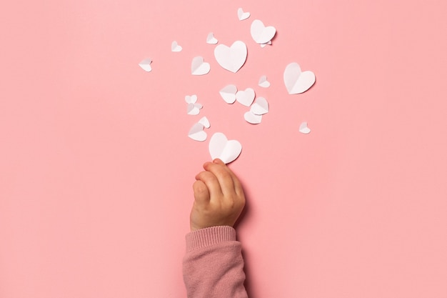 Child's hand takes a valentine card from paper on a pink background. composition valentine's day. banner. flat lay, top view.