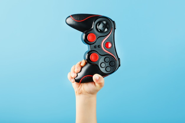 Child's hand triumphantly holds the gamepad on a blue surface