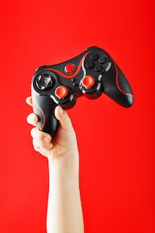 Child's hand triumphantly holds the gamepad on a red surface