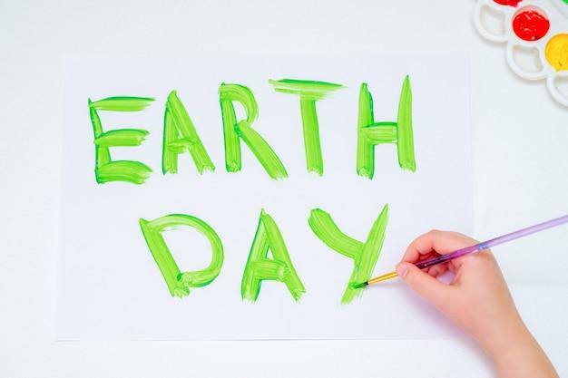 흰 종이에 녹색 수채화로 지구의 날이라는 단어를 쓰는 어린이의 손. 지구의 날 개념입니다.