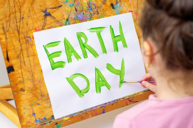 이젤에 흰 종이에 녹색 수채화로 지구의 날이라는 단어를 쓰는 어린이의 손. 지구의 날 개념입니다.