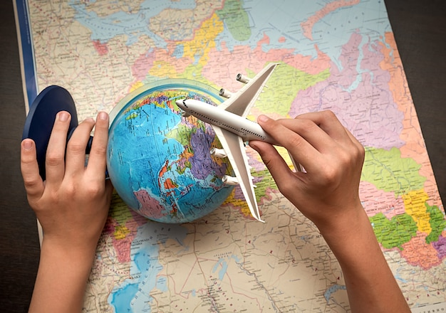 子供の手は地球儀と飛行機を持っています。世界地図の背景。旅行のコンセプト。